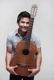 Asiatischer Kursteilnehmer, der eine Gitarre anhält Stockbilder