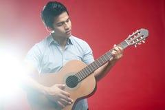 Asiatischer Kursteilnehmer, der Gitarre spielt Lizenzfreies Stockbild