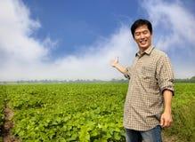 Asiatischer Landwirt, der seinen Bauernhof zeigt lizenzfreies stockfoto