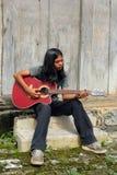 Asiatischer langhaariger Junge, der Gitarre spielt. Lizenzfreies Stockfoto