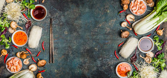 Asiatischer Lebensmittelhintergrund mit verschiedenem vom Kochen von Bestandteilen auf rustikalem Hintergrund, Draufsicht