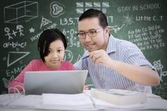 Asiatischer Lehrer unterrichtet seinen Studenten, einen Laptop zu benutzen lizenzfreies stockbild