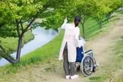 Asiatischer älterer Mann, der auf einem Rollstuhl mit dem Pflegekraftzeigen sitzt Stockbild