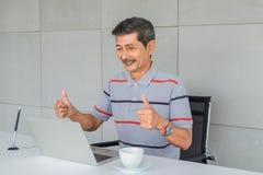 Asiatischer ?lterer Mann Froh, Aufzug beide Daumen Sitzender Blick auf zu Laptop-Computer Schirm stockfotos