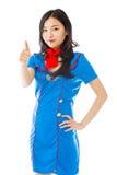 Asiatischer Luftstewardess, der Daumen herauf das Zeichen steht mit der Hand auf Hüfte herstellt Lizenzfreies Stockfoto