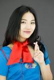 Asiatischer Luftstewardess, der ihre Finger kreuzt Lizenzfreie Stockfotos