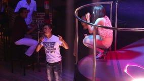 Asiatischer Mädchensänger sitzt auf Stadium am Impresario, der Stern einführt stock footage
