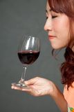 Asiatischer Mädchenabschluß ihre Augen und Gerucharoma des Rotweins Stockbilder