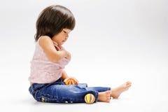 Asiatischer Mädchensitzen- und -spielfarbball stockbild