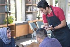 Asiatischer männlicher Kellner schreiben Aufträge von den costumers am Café in Hintergrund stockbild
