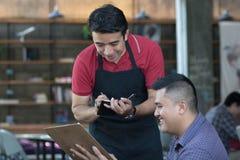 Asiatischer männlicher Kellner schreiben Aufträge von den costumers am Café in Hintergrund lizenzfreie stockfotografie