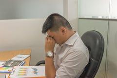 Asiatischer Manager erschöpft und frustriert nach der Prüfung vieler Verkaufsberichte stockfotos