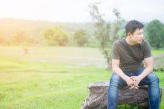 Asiatischer Mann, allein sitzend auf der Bank Die grüne Wiese und der Berg des Hintergrundes lizenzfreies stockbild