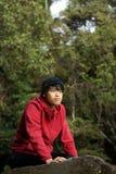 Asiatischer Mann, der auf Felsen knit Stockfotografie