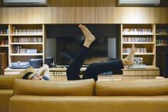 Asiatischer Mann, der auf Sofa im Wohnzimmer nachts legt lizenzfreies stockfoto