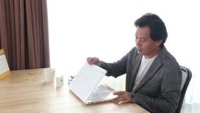 Asiatischer Mann, der aus dem Rahmen heraus nach Ende seins Arbeit über Laptop geht stock video footage