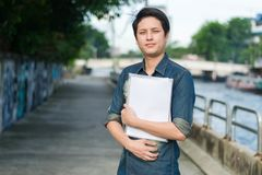 Asiatischer Mann, der Belegdatei steht und hält lizenzfreie stockfotos