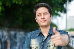 Asiatischer Mann, der Daumen steht und sich zeigt lizenzfreies stockbild