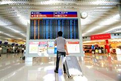 Asiatischer Mann, der den Flug auf dem Abfahrtszeitbrett an internationalem Flughafen Hong Kongs steht und hält Gepäck und überpr Lizenzfreie Stockfotos