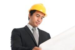 Asiatischer Mann, der den gelben Hardhat schaut Blaupausenpapier trägt Stockfoto