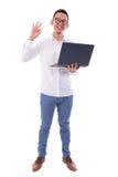 Asiatischer Mann, der den Laptop zeigt okayzeichen verwendet Stockbilder