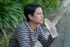 Asiatischer Mann, der eine Flasche Wasser sitzt und trinkt lizenzfreie stockfotografie