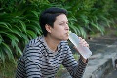 Asiatischer Mann, der eine Flasche Wasser sitzt und trinkt lizenzfreie stockbilder