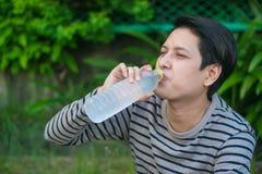 Asiatischer Mann, der eine Flasche Wasser sitzt und trinkt stockbild