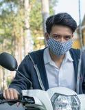Asiatischer Mann, der eine Maske trägt, um Verkehrsverschmutzung zu vermindern Stockbilder