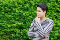Asiatischer Mann, der etwas steht und denkt lizenzfreies stockfoto