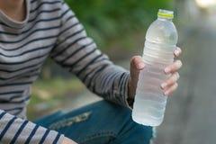 Asiatischer Mann, der Flasche Wasser sitzt und hält lizenzfreies stockbild