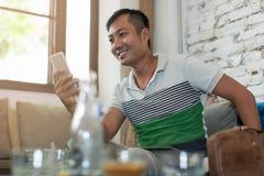 Asiatischer Mann, der Handy-Lächeln-sitzendes Café verwendet Stockfotografie