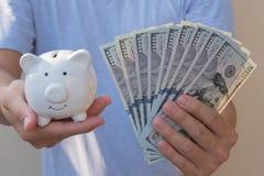 Asiatischer Mann, der hundert Dollarschein h?lt Wohlhabendes und Reichtumskonzept lizenzfreie stockfotos