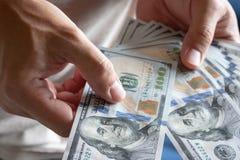Asiatischer Mann, der hundert Dollarschein h?lt Wohlhabendes und Reichtumskonzept lizenzfreie stockfotografie