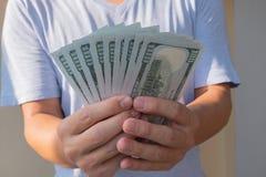Asiatischer Mann, der hundert Dollarschein h?lt Wohlhabendes und Reichtumskonzept stockfotografie