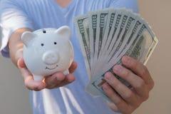 Asiatischer Mann, der hundert Dollarschein h?lt Wohlhabendes und Reichtumskonzept stockfotos