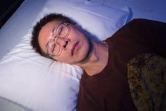 Asiatischer Mann, der an im Bett mit seinen Augengläsern schläft stockbild