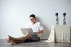 Asiatischer Mann, der Laptop verwendet Lizenzfreie Stockfotos
