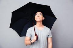 Asiatischer Mann, der mit Regenschirm steht und oben schaut Stockfotos