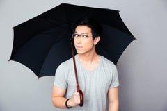 Asiatischer Mann, der mit Regenschirm steht und weg schaut Lizenzfreie Stockbilder