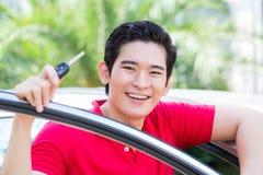Asiatischer Mann, der Schlüssel seines Autos zeigt Stockfotos