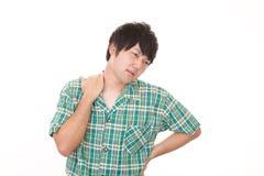 Asiatischer Mann, der Schulterschmerz hat stockfoto