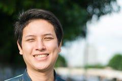 Asiatischer Mann, der sein glückliches Lächeln steht und zeigt stockbild