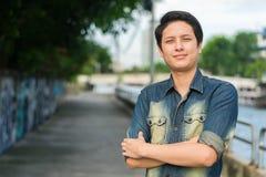 Asiatischer Mann, der sein glückliches Lächeln steht und zeigt stockfotografie