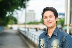 Asiatischer Mann, der sein glückliches Lächeln steht und zeigt lizenzfreies stockbild