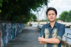 Asiatischer Mann, der sein glattes Gesicht steht und zeigt lizenzfreie stockfotografie