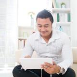 Asiatischer Mann, der Tabletten-PC verwendet Stockfoto