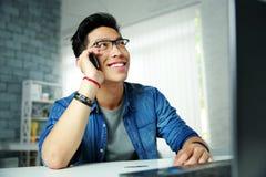 Asiatischer Mann, der am Telefon an seinem Arbeitsplatz spricht Stockfoto