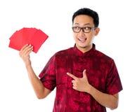 Asiatischer Mann, der vielen rotes Paket zeigt Stockfoto