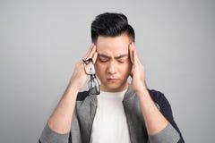 Asiatischer Mann des frustrierten Geschäfts mit Kopfschmerzen - lokalisiert über GR stockbild